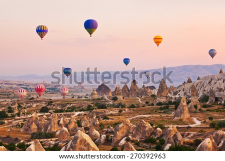 Hot air balloon flying over rock landscape at Cappadocia Turkey - stock photo
