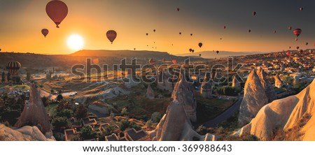 Hot air balloon flying over spectacular Cappadocia - stock photo