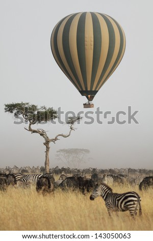 Hot air balloon flying over the african savannah - stock photo