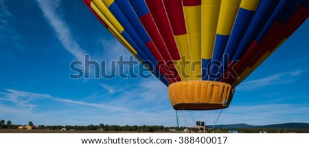 hot air balloon lifting off in the rocky mountain of Colorado with a nice blue sky background with a colorful yellow blue and red balloon close up - stock photo