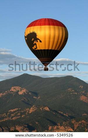 Hot air balloon over mountain - stock photo