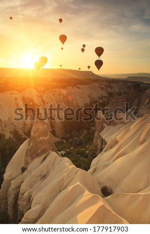 Hot air balloon over rock formations in Cappadocia, Turkey  - stock photo
