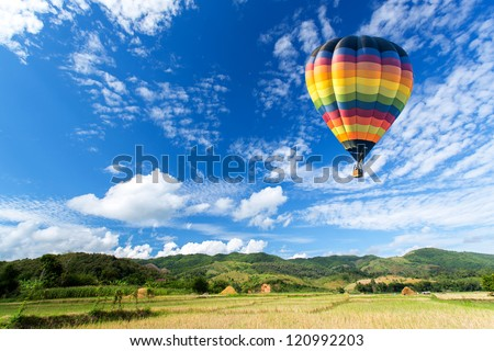 Hot air balloon over the field with blue sky - stock photo