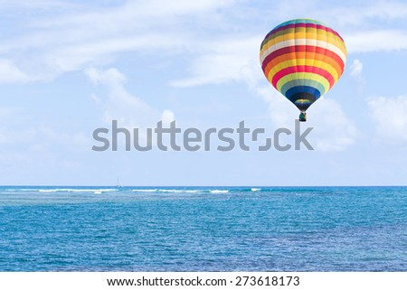 Hot air balloon over the sea and blue sky background  - stock photo