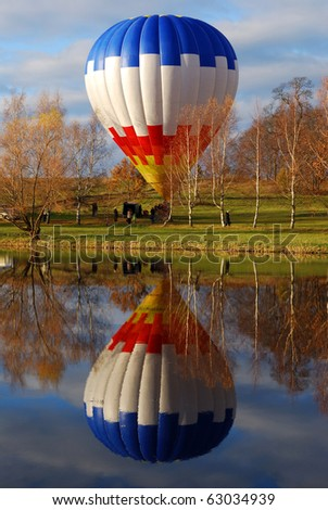 Hot air balloon reflecting in a lake in autumn - stock photo