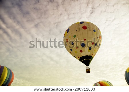 Hot air balloon rising up to the enchanting morning sky - stock photo