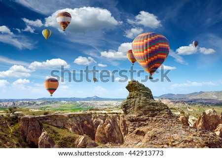 Hot air ballooning is most amazing attraction and adventure in Kapadokya. Colorful hot air balloons flies above rocks in Cappadocia, Turkey - stock photo