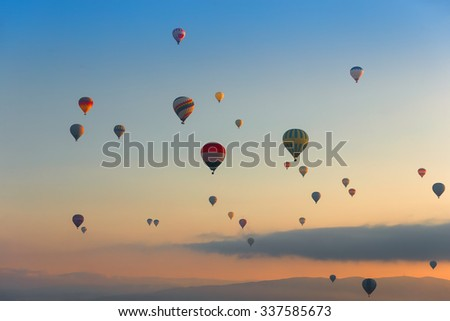 Hot air balloons (atmosphere ballons) flying over mountain landscape at Cappadocia in the sunrise (UNESCO World Heritage Site since 1985) - Turkey - stock photo