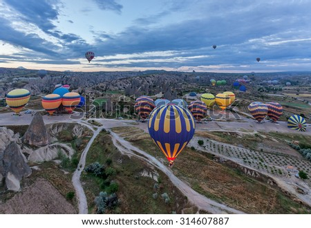 Hot air balloons (atmosphere ballons) flying over mountain landscape at Cappadocia, UNESCO World Heritage Site since 1985) - Turkey - stock photo