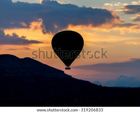 Hot air balloons (atmosphere ballons) flying over mountain landscape in the  Cappadocia at sunset, UNESCO World Heritage Site since 1985) - Turkey - stock photo