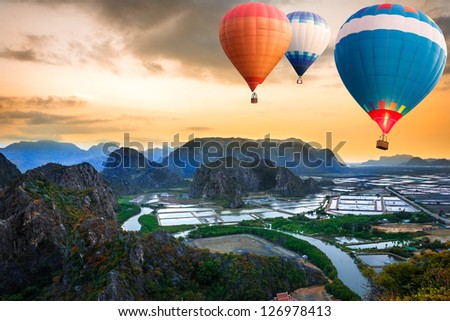 Hot air balloons floating up to the sky over mountain - stock photo