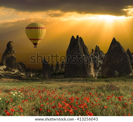 Hot air balloons flying over a field of poppies and rock landscape at Cappadocia, Turkey - stock photo