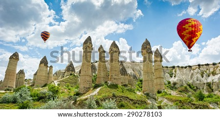 Hot air balloons flying over Love valley at Cappadocia, Anatolia, Turkey. Volcanic mountains in Goreme national park. - stock photo