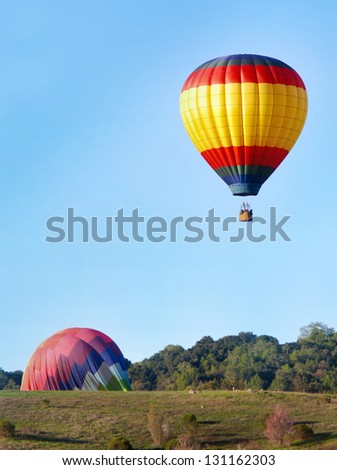 Hot air balloons landing in green hills with trees - stock photo