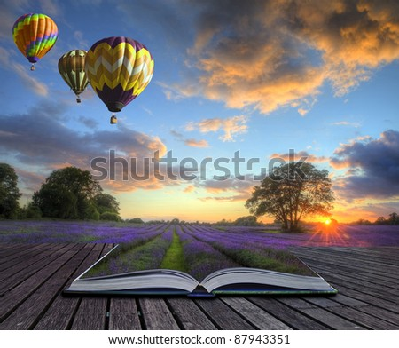 Hot air balloons over Summer lavender field landscape coming out of pages in magic book - stock photo