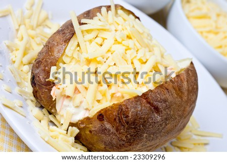 Hot and crispy baked potato stuffed with cheddar cheese and coleslaw - stock photo