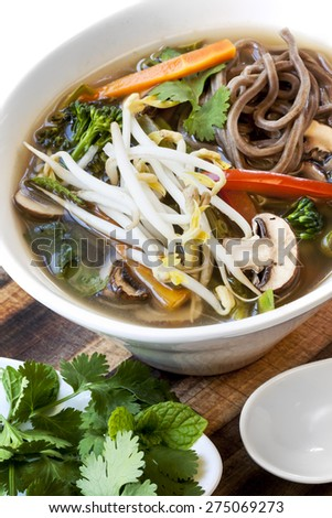 Hot and sour vegetable soup with soba noodles and bean sprouts.  Garnished with mint and coriander or cilantro. - stock photo