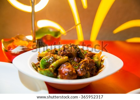 hot and spicy chicken chilli in a serving bowl in a restaurent shot in dim lighting at high ISO - stock photo