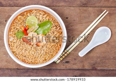 Hot and spicy instant noodle on the wood background - stock photo
