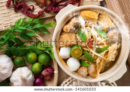 Hot and spicy Singaporean Curry Noodle or laksa  mee with hot steam in clay pot, decoration setup, serve with chopsticks. Singapore cuisine. - stock photo