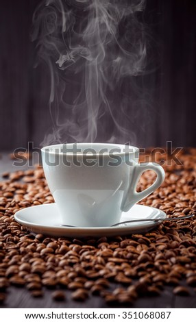 Hot aromatic coffee drink in the white cup with saucer and spoon with beans background - stock photo