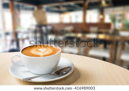 Hot art Latte Coffee in a cup on wooden table and Coffee shop blur background with bokeh image. - stock photo