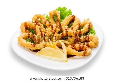 Hot asian restaurant snack - deep fried calamari rings with lemon served on a white square plate isolated at white background - stock photo
