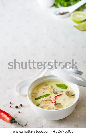hot asian soup with coconut milk served on the white table-cloth - stock photo