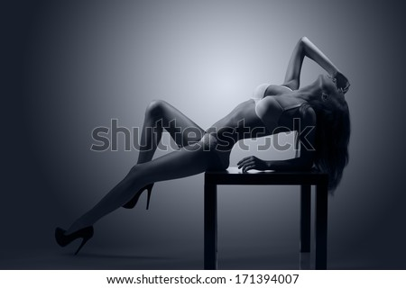 hot backlight portrait of alluring girl posing on small table with sexy white lingerie showing her perfect body  - stock photo