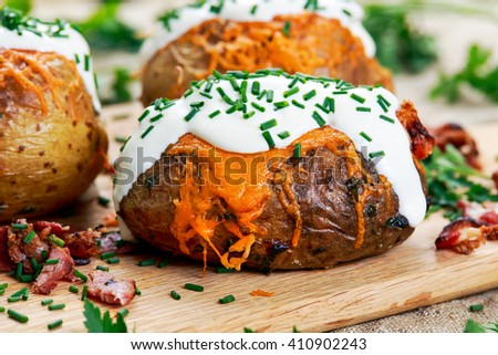 Hot Baked Potato with cheese, bacon, chives and sour cream. - stock photo