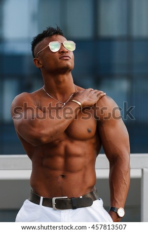 Hot beautiful black man with muscular body on the background of the urban landscape. Handsome Shirtless Hunk man outdoor in the city, without a shirt, showing his muscles. Black guy with a naked torso - stock photo
