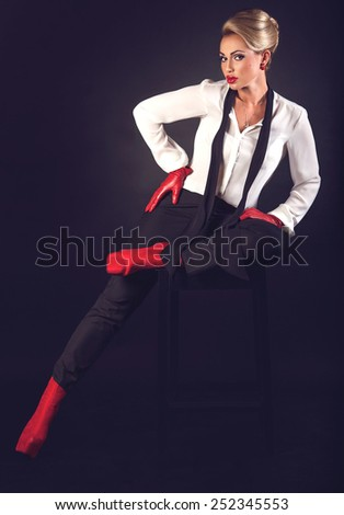 Hot beautiful blonde woman with red plump lips in black pants, white shirt and red shoes sexy posing on dark background with copy space  - stock photo