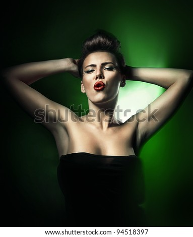 hot beautiful woman with red lips in dark green light - stock photo