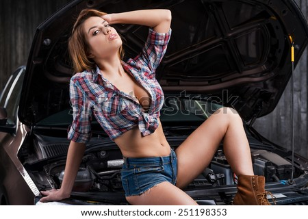 Hot beauty. Attractive young woman with beautiful cleavage holding hand in hair while leaning at the car in auto repair shop - stock photo