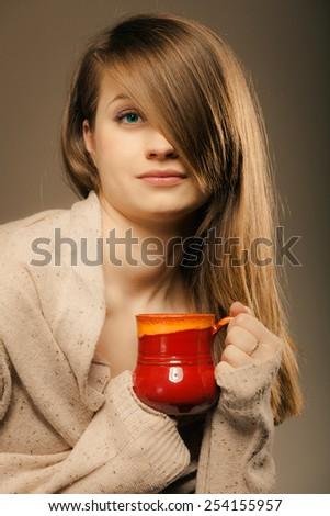 Hot beverage. Sleepy girl holding cup mug of drink tea or coffee. Woman in warm sweater warming herself - stock photo