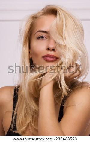 Hot blonde girl posing in white room - stock photo