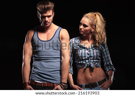 Hot blonde woman with her hands in pocket looking at her boyfriend while he is looking at the camera. - stock photo