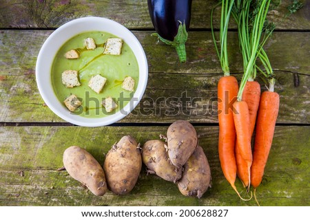 Hot bowl of pea soup with croutons with raw new potatoes, carrots and aubergine on a rustic wooden background - stock photo