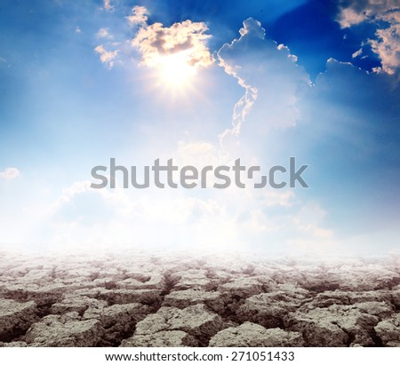Hot bright sun over cloudy sky with broken land soil - stock photo