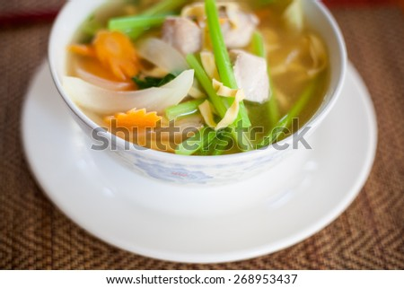 Hot cambodian broth with fish and vegetables. Traditional khmer style soup. - stock photo