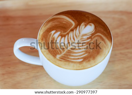 hot cappuccino coffee latte arts in leaves shape in white cup on wood plate - stock photo