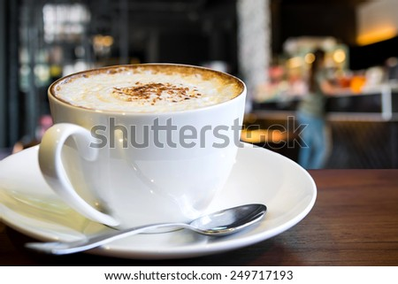 Hot Cappuccino cup with coffee shop background  - stock photo