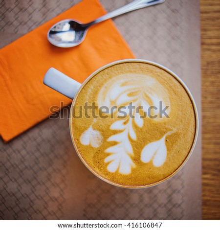 Hot Cappuccino on the table in cafe, warm vintage tone, top view. - stock photo