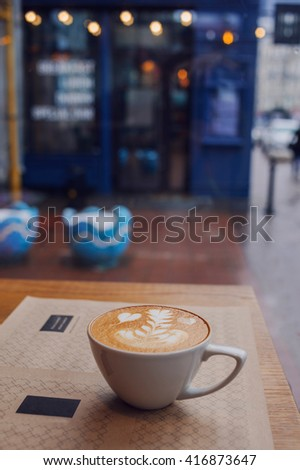 Hot Cappuccino on the table in cafe with blur coffee shop background, warm vintage tone, evening or early morning.  - stock photo