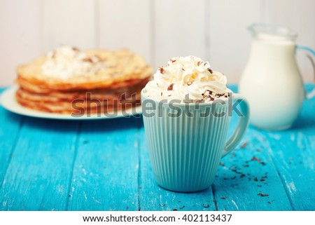 Hot cappuccino with delicious cream and chocolate scattered  and pancakes on a blue wooden background. Morning breakfast.  - stock photo
