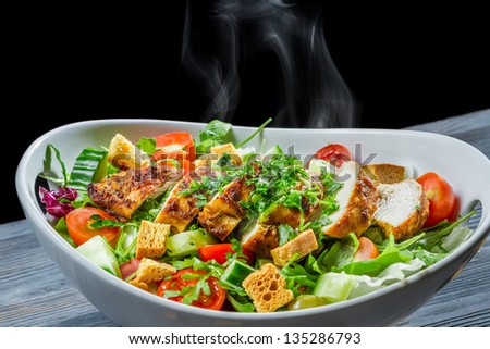 Hot chicken and fresh vegetables in healthy salad - stock photo