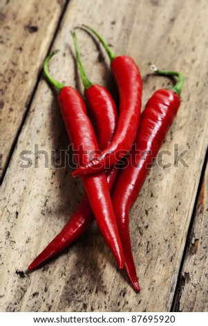 hot chili peppers on wooden desk - stock photo