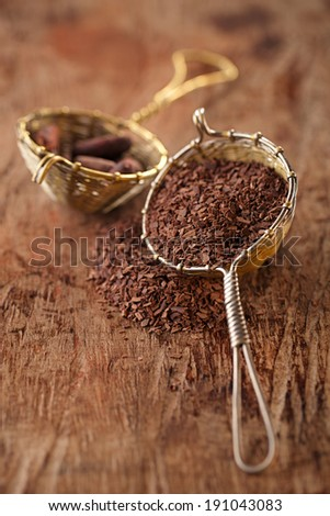 hot chocolate flakes with chilli flavor in old rustic style silver sieve, shallow dof - stock photo