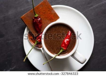 Hot chocolate in a white cup and red chili peppers on a dark stone background - stock photo