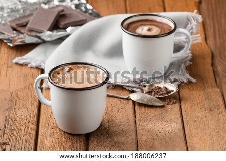 Hot chocolate with foam in two enamel mugs - stock photo